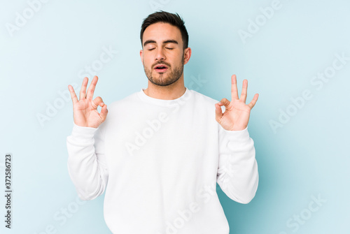 Fototapeta Young caucasian man isolated on blue background relaxes after hard working day, she is performing yoga
