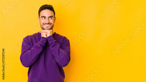 Photo Young caucasian man isolated on yellow bakground keeps hands under chin, is looking happily aside