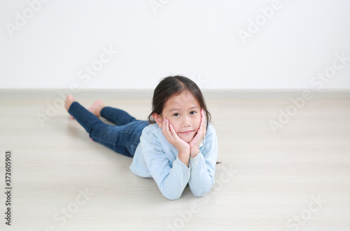 Portrait asian little child girl lying on wood laminate flooring in the room with looking at camera Canvas-taulu