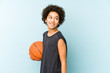 Kid boy playing basketball isolated on blue background looks aside smiling, cheerful and pleasant.