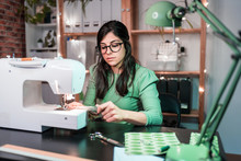 Slim Female Tailor In Casual Wear Using Sewing Machine While Sitting In Table With Sewing Machine In Loft Style Atelier