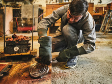 Professional Mature Craftsman In Workwear And Protective Gloves Cleaning Metal Casting Removed From Sand Mold While Working In Goldsmith Workshop