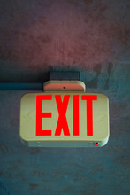 Illuminating Rectangular Bright Red Exit Sign Attached To Shabby Concrete Ceiling In Dark Room