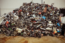 Dump Of Pile Of Different Old Multicolored Metal Parts For Recycling On Brown Floor Near Cement Wall