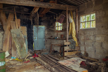 Interior Of Abandoned Fisherman House With Metal Door And Brick Wall With Outfit And Different Wooden Boards With Shabby Surface In Daylight