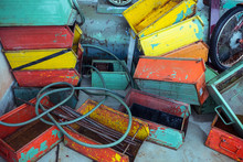 From Above Of Heap Of Used Colorful Rectangular Metal Boxes With Shabby And Rusty Surface Near Cable And Bike Wheel On Floor In Garage