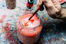 From Above Crop Anonymous Male Artist Washing Paintbrush Off In Jar With Colored Water Above Worktop In Studio