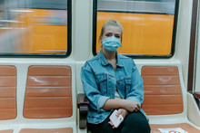 Millennial Female Passenger In Casual Outfit And Protective Mask Looking At Camera Sitting Alone Inside Underground Train With Prohibition Signs On Seats For Keeping Distance During Coronavirus Pandemic