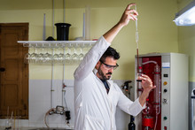 Side View Of Bearded Male Chemist In White Robe Pouring Red Liquid Into Transparent Flask From Long Tube While Standing Near Distillation Equipment In Lab