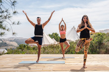 Group Of Full Body Man And Women In Activewear Demonstrating Ways To Practice Yoga In Tree Pose For People With Different Levels While Standing On Mats On Wooden Platform On Nature Against Tents And Plants And Mountains