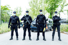 Full Body Squad Of Spanish Police Officers In Protective Gears With Guns Wearing Medical Masks During Patrolling Street