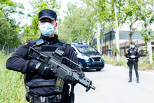 Concentrated Police Officer In Uniform And Medical Mask Looking Away While Patrolling Street With Automatic Rifle