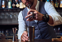 Cropped Unrecognizable Professional Barman In Elegant Suit Using Long Spoon To Mix Alcohol Liquid In Metal Shaker While Preparing Cocktail In Bar