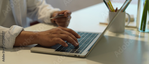 Side view of a man holding credit card while online paying with laptop on workta Wallpaper Mural