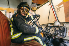 Side View Of Unrecognizable Firefighter In Uniform And Helmet Touching Steering Wheel And Transmission While Sitting On Leather Seat In Aged Fire Truck Near Speedometer