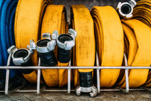 Kit Of Yellow Rolled Dirty Fire Hoses Made Of High Strength Materials With Metal Mandrels On Edges On Metal Shelf In Fire Truck