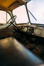 Interior Of Aged Fire Truck With Steering Wheel And Speedometer With Arrows Above Large Leather Seat In Front Of Windshield With Wipers And Side Mirror
