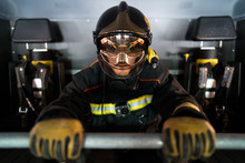 From Above Of Anonymous Firefighter In Heat Resistant Gloves And Protective Helmet Sitting In Fire Truck Near Seats With Safety Vests