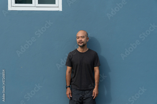 Fotomural portrait of Asia bald beard 40s man in casual cloth on blue wall background