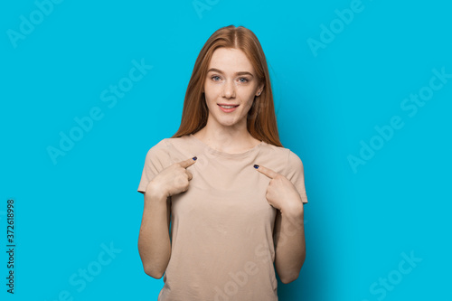 Papel de parede Confident caucasian woman with red hair and freckles posing on a blue wall is po