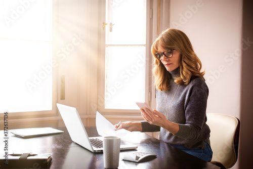 Obraz Shot of mature businesswoman sitting at desk while working from home - fototapety do salonu