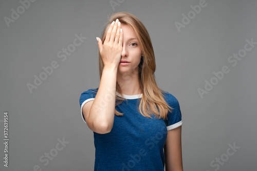 Photo of tired Young female with blond hair, covers face, feels fatigue, needs good rest, dressed in blue t shirt, isolated over gray background Canvas Print
