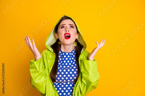 Fototapeta Portrait of mad angry girl look copyspace dislike rain fall wear green raincoat