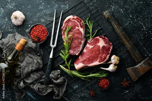 Fototapeta Raw meat, beef steak on dark background. Top view. Free space for your text. obraz na płótnie