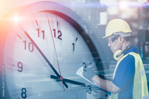Obraz Engineer worker looking service check list in factory overlay with time clock for working hours concept. - fototapety do salonu