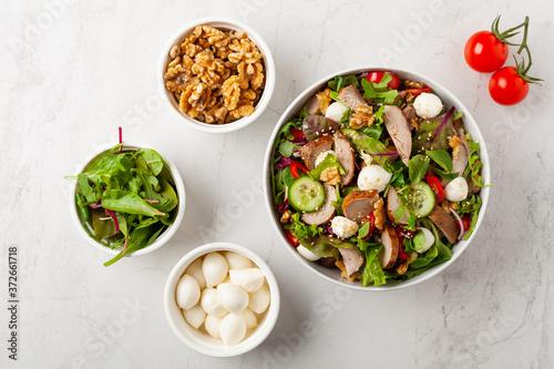 Fotografering Salad with pork tenderloin, fresh cucumber and mozzarella.