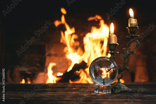Obraz Crystal ball on the magic table on a burning fire background. Future reading. - fototapety do salonu