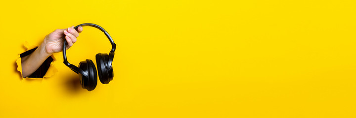 Female hand holding headphones on a bright yellow background. Banner.