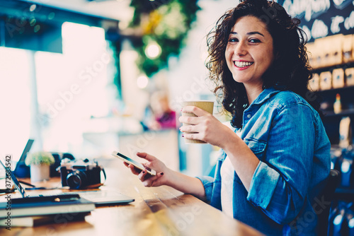 Fototapeta Half length portrait of smiling hipster girl with curly hair laughing while having working break indoors