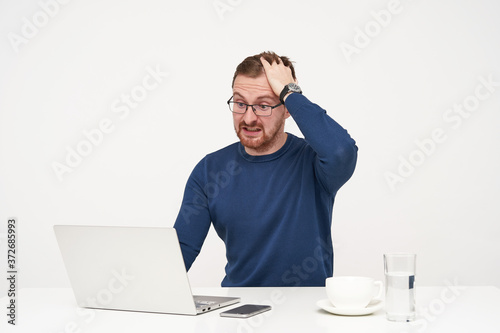 Photo Agitated young pretty bearded male in glasses rumpling his hair while looking am