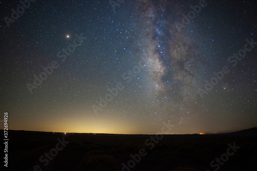 Fotografiet Milky Way stars above a vast prairie with a distant fire