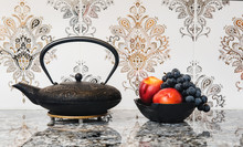 Tea Pot And Bowl Of Fruit Against A Tile Background
