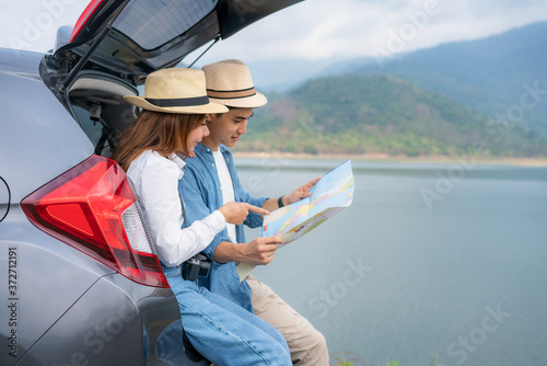 Papel de parede Portrait of Asian couple sitting in car with man pointing to view and woman looking beautiful landscape and holding maps while vacation together in holiday