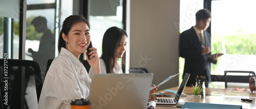 Portrait shot young businesswoman calling her phone and looking at camera Canvas