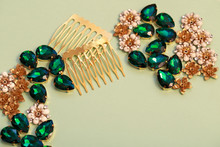 Materials For Creating Jewelry. Emerald Green Rhinestones, Hair Comb Bases And Metal Flowers On A Plain Paper Background