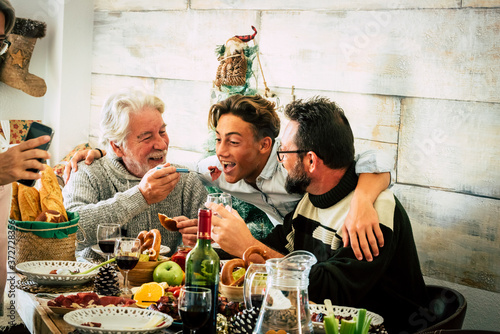Foto Happy family men enjoy together christmas lunch at home - mixed agesd generation