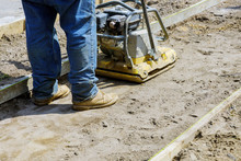 Vibrating Hammer, With Sand Jumping In Process In The During Sidewalk