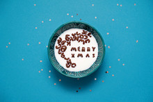 Top View Of Bowl With Milk And Chocolate Alphabet Cereals. Merry Xmas Text. Blue Background