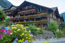 A Hotel Decorated With Flags, Cow Bells And Flowers In The Village Of Lauterbrunnen, Switzerland