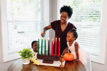 Black Mother Lighting Kwanza Candles