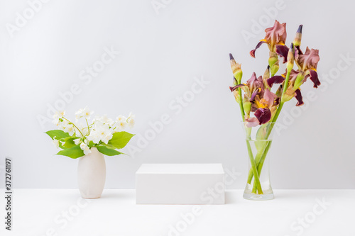 Empty white box and bouquet of irises flowers in a glass vase on a light background Slika na platnu