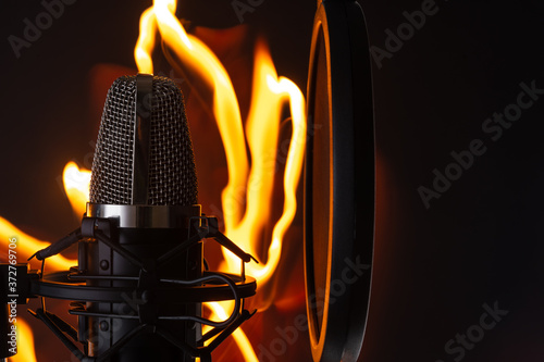 Black professional studio microphone on fire background, recording vocals or sound