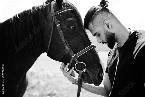 Fotografie, Tablou Arab tall beard man wear in black with arabian horse.