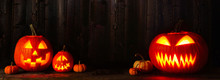 Halloween Jack O Lanterns At Night. Banner With Copy Space Against A Dark Wood Background.