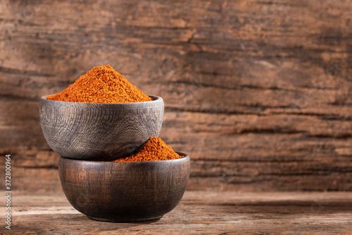 Fotografija Paprika powder in a wooden bowl - Capsicum annuum