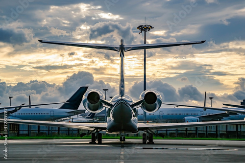 Fototapeta Private business jet parking at parking stand under sunset